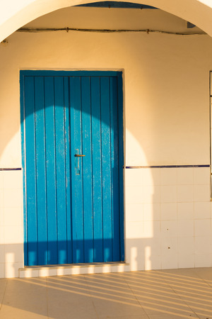 Blue wooden door on a sunny Mediterranean front porch photo