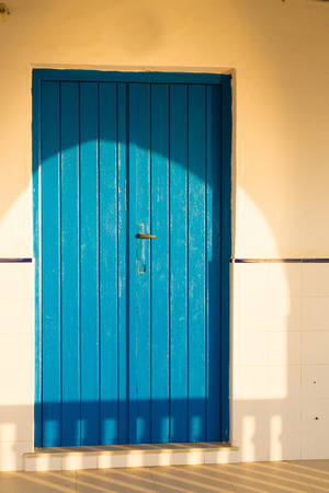 front porch: Blue wooden door on a sunny Mediterranean front porch