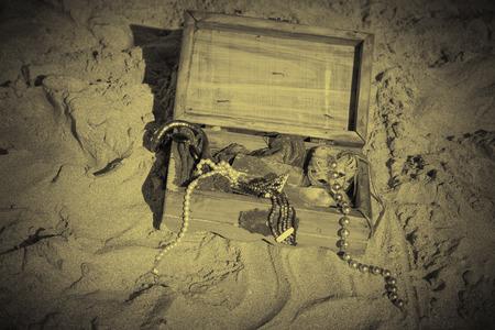 suelo arenoso: Pecho de tesoro con la tapa abierta excavado en el suelo arenoso
