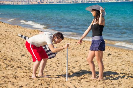 bossy: Bossy girl ordering her boyfriend around to set up  a sunshade on the beach