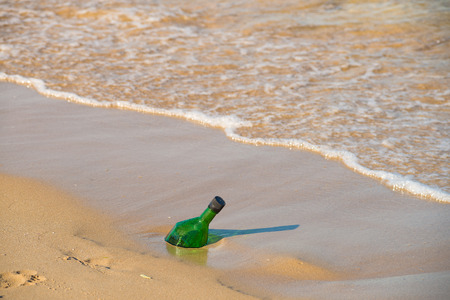 ashore: Green glass bottle washed ashore, will it contain a message