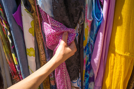 Female hands choosing clothes at a garage sale photo
