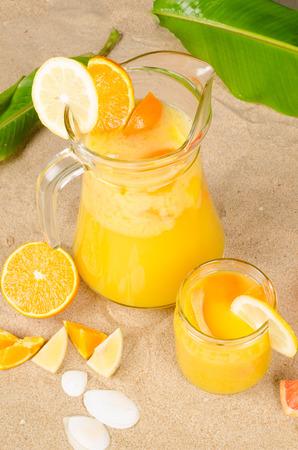 Freshly squeezed fruit juice on beach snad photo