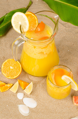 Freshly squeezed fruit juice on beach snad photo