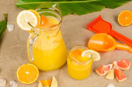 Freshly squeezed fruit juice on beach sand photo