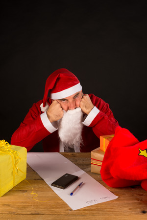 miserable: Grumpy Santa leaning exhausted on his office desk