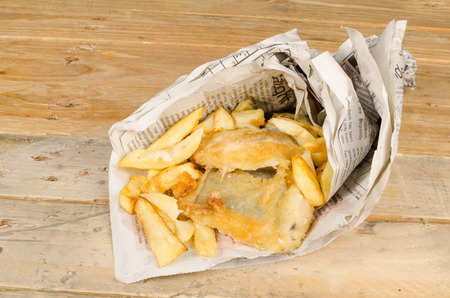 Traditional fish and chips wrapped in a newspaper cone photo