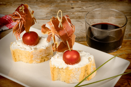 finger food: Serrano ham tapa served on bread with goat cheese