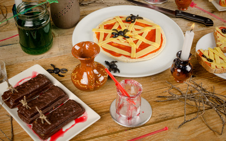 Assorted creative Halloween party food on a wooden table photo
