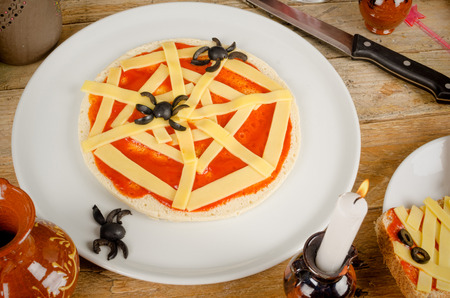 Halloween pizza decorated as a spider web, a kid party meal photo