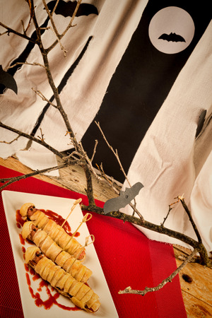 Sausages wrapped in dough in the shape of mummies, a Halloween kid party snack photo