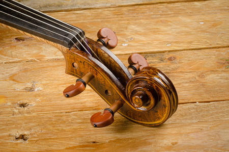 Violin neck displayed on a rustic wooden background Stock Photo