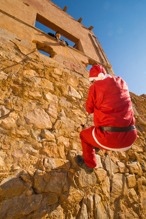 Santa climbing a wall while a scary Halloween monster is waiting for him photo