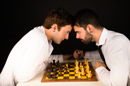 chess board: Two guys in their 20s clashing over a chess board Stock Photo