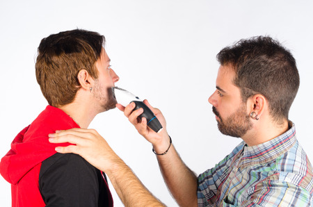 shorten: Barber trimming a beard with an electric razor Stock Photo