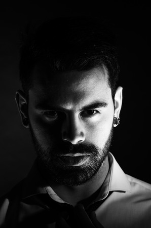 Black and white portrait of a bearded man in his 20s