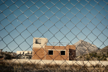 fenced: Fenced building site with abandoned unfinished houses Stock Photo