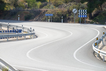 single lane road: A tight bend in a road with crash barriers Stock Photo