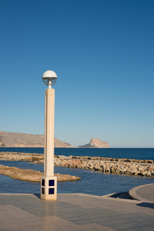 altea: Sunny Altea beach promenade with Calpe in the background, Costa Blanca, Spain Stock Photo