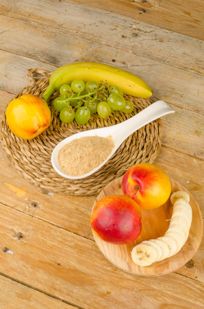 brewers: A spoon full of brewers yeast surrounded by fresh fruit Stock Photo