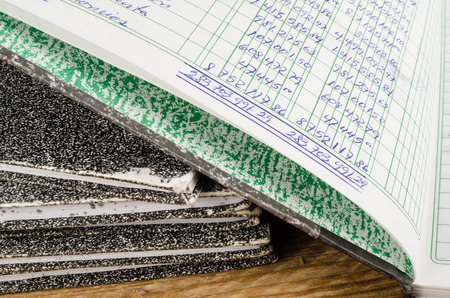 ledger: Old  ledger books,  the top one open and dislpaying handwriting