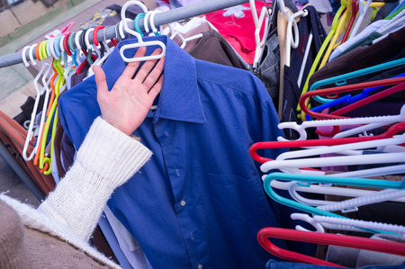 market stall: Female hands choosing clothes on a market stall