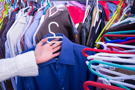 blouses: Female hands choosing clothes on a market stall