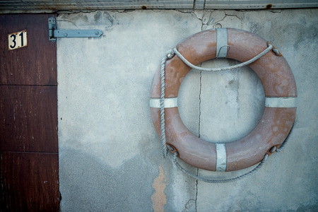 life belt: Old life belt hanging on the wall of a pier