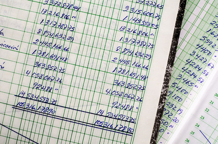 financials: Handwritten accounting on the open pages of some old ledgers