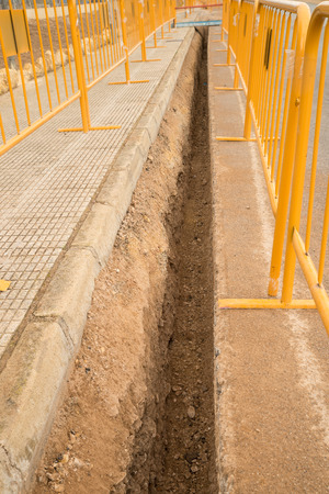 ditch: Roadworks with a ditch for a pipeline protected by a barrier