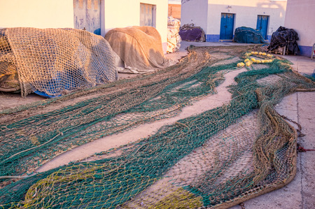 fishing nets: Several fishing nets spread out on a dock to be repaired