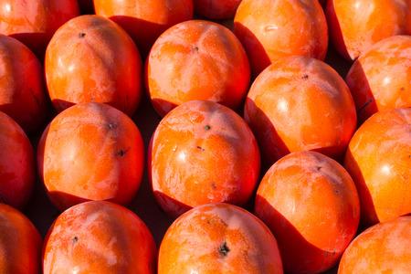 market stall: Full frame take of ripe persimon on a street market stall