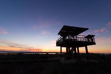 watchtower: Wooden wildlife observation watchtower against the background of a sunrise