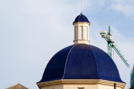Church dome and a  construction crane, a restoration concept