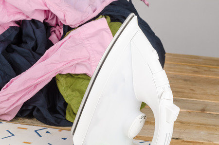 messy clothes: Iron and a big heap of messy, crumpled clothes