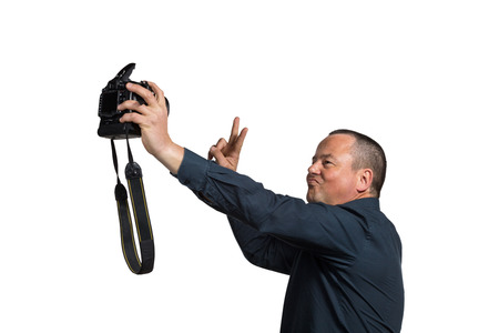 narcissistic: Guy in his 40s fooling around with too big a camera for a selfie Stock Photo