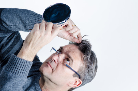 midlife: Guy checking out his hair with a mirror