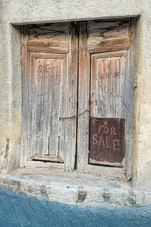 crunch: For sale handwriten on a derelict door, a real estate crunch concept