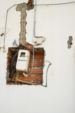 electricity meter: Unfinished wiring and electricity meter on a wall
