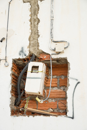 uncompleted: Unfinished wiring and electricity meter on a wall