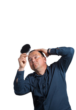 balding: Worried guy having a closer look at his balding head
