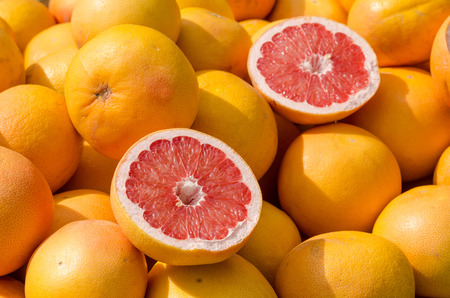Full frame take of many grapefruit on a street market stall