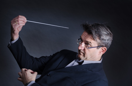 baton: Conductor with a mad expression fidgeting with his baton