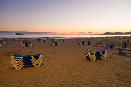piled: Benidorm beach with deckchairs neatly piled up at the end of a sunny day