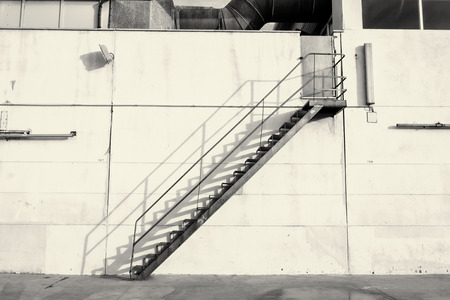 metal handrail: Industrial staircase against an exterior concrete wall