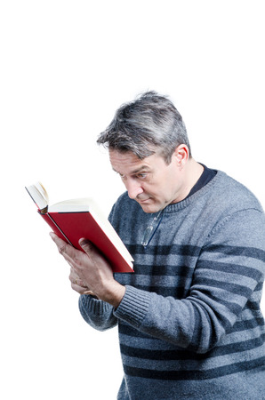 shortsightedness: Guy having to hold a book very close, a myopia concept Stock Photo