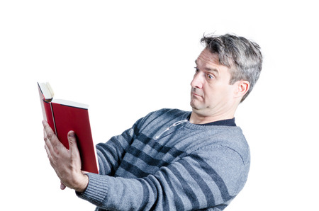 Guy finding holding a book at quite a distance to be able to read