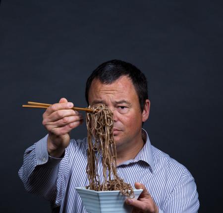 Guy immer ziemlich mit seinen Versuchen, auf das Essen mit Stäbchen gefüttert