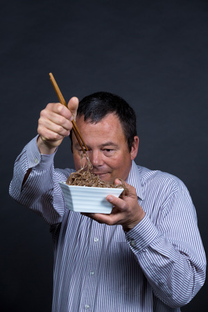 fed up: Guy getting pretty fed up with his attempts on eating with chopsticks