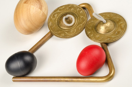 triangle musical instrument: An assortment of small percussion instruments on white